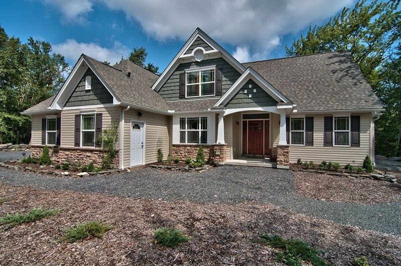 Custom home front exterior with tan siding, dark green shake and pillared entrance