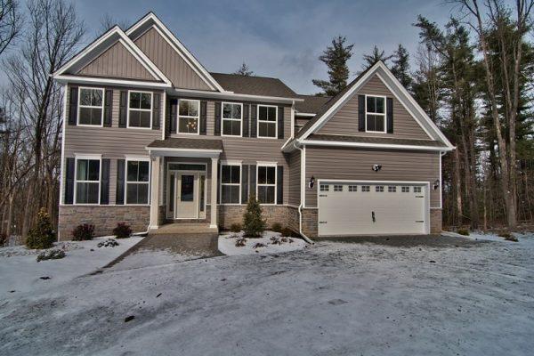Jamison home front exterior with light grey siding, 2 car garage, light snow